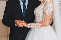 Slim beautiful young bride holding her father`s hand before her wedding royalty free stock images