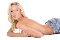 Slim beauty. Beautiful tanned slim blond girl in blue jeans lying on white background Stock Images