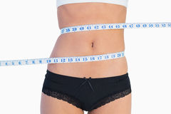 Slim belly surrounded by measuring tape. On white background Royalty Free Stock Image