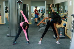 Slim black african-american fitness instructor shows to asian lovely woman how to do exercises. Gym background Stock Image