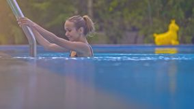 Slim Blond Girl Plunges into Pool against Green Plants Closeup. Closeup side view slim blond girl with ponytail in bikini plunges into pool holding handrails stock video