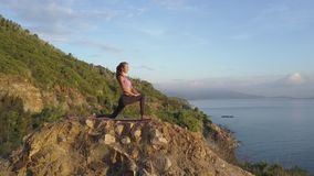 Slim blond girl stands in warrior pose on stone against hill sea. Young slim blond girl stands in warrior pose on large stone against green hill blue sky and stock footage