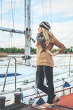 Slim blond standing next to a yacht Stock Photography