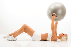 Slim blond woman exercises with fitness ball Royalty Free Stock Image
