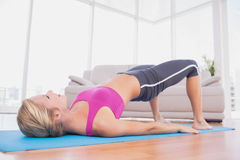 Slim blonde doing pilates on exercise mat Royalty Free Stock Image