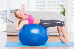 Slim blonde doing sit ups on exercise ball smiling at camera Royalty Free Stock Photography