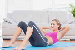 Slim blonde doing sit ups on exercise mat Royalty Free Stock Photo