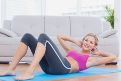 Slim blonde doing sit ups on exercise mat smiling at camera Stock Images
