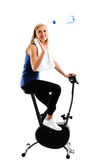 Slim blonde girl catching a bottle. Of mineral water or other drink while training on exercise stationary bike Stock Photos