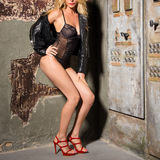 Slim blonde girl posing in black lingerie, leather jacket and red high heels near the electrical panel and the old wall Stock Photography