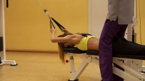 Slim blonde girl working out in a gym with coach stock video