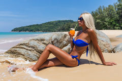 Slim blonde long haired woman bikini orange cocktail tropical be Royalty Free Stock Image