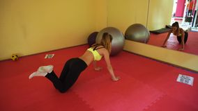 Slim blonde sports girl in tight clothes training in a gym. Healthy lifestyle stock footage