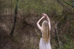 Slim blonde in white - black dress is back in a graceful pose. On a background pvesennego ravine. Spread out in the side of the hand. Long luxuriant golden hair Stock Photo