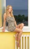 Slim blonde on the windowsill Stock Images