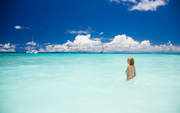 Slim blonde woman enjoys the turquoise ocean in Seychelles. Blue sky with white clouds, greenish blue water and a beautiful lady with sailing ships Stock Photos