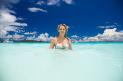 Slim blonde woman enjoys the turquoise ocean in Seychelles. Blue sky with white clouds, greenish blue water and a beautiful lady with sailing ships Royalty Free Stock Photo