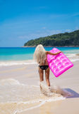Slim blonde woman with pink swimming mattress on tropical beach Stock Photography