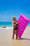 Slim blonde woman with pink swimming mattress on tropical beach Stock Image