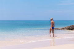 Slim blonde woman swimming in clear water on tropic beach Royalty Free Stock Images