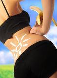 Slim body. Of a young girl with banaba with cream sun on it stock image