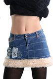 Slim body. The girl in a jeans skirt shows a stomach Stock Photography