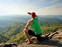 Slim body hiker in green singlet and black shorts sit on a rock, enjoy natural scenery. View into forest valley Stock Photos