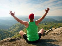 Slim body hiker in green singlet and black shorts sit on a rock, enjoy natural scenery. View into forest valley Royalty Free Stock Images