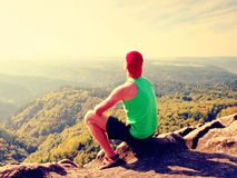 Slim body hiker in green singlet and black shorts sit on a rock, enjoy natural scenery. View into forest valley Stock Photo
