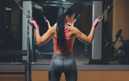 Slim, bodybuilder girl, does the exercises standing in front of the mirror in the gym. Sports concept, fat burning and a healthy lifestyle Royalty Free Stock Images