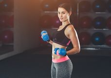 Slim, bodybuilder girl, lifts dumbbell standing in front of the mirror while training in the gym. royalty free stock image