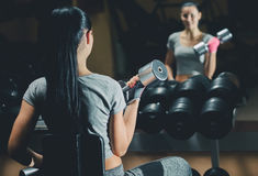 Slim bodybuilder girl lifts heavy dumbbell standing in front of the mirror while training in the gym. Stock Photos