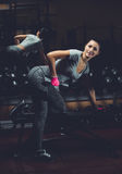 Slim, bodybuilder girl, lifts heavy dumbbell standing in front of the mirror while training in the gym. Royalty Free Stock Photos