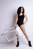 Slim brunette girl with curly hair in the body is a white stool in her hand Royalty Free Stock Photos