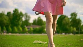 Slim brunette girl in pink dress walks at camera. Slow motion steadicam clip stock footage