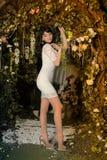 Slim brunette girl. In a short white dress Royalty Free Stock Photography