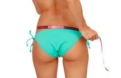 Slim brunette girl with tape measure in bikini royalty free stock image