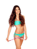 Slim brunette girl with tape measure in bikini Royalty Free Stock Photography
