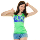 Slim brunette in green T-shirt and shorts thumb up. Royalty Free Stock Images