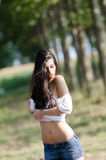 Slim brunette lady with long hair playing with her shirt and reveals her flat belly Royalty Free Stock Image