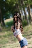 Slim brunette lady with long hair playing with her shirt and reveals her flat belly Stock Image