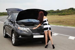 Slim brunette near broken car on the road Stock Photo
