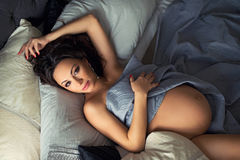 Slim brunette pregnant woman lying  on a beautiful bed linen. Stock Photo
