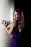 Slim brunette in purple dress posing near column Royalty Free Stock Photography