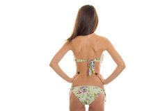Slim brunette woman with beautiful round buttocks in swimsuit with floral pattern posing from behind isolated on white Royalty Free Stock Images