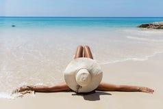 Slim brunette woman in hat sunslasses sunbathe on the beach Royalty Free Stock Photography
