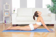 Slim brunette woman lying in yoga pose in her living room Royalty Free Stock Image