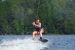 Slim brunette woman riding wakeboard on lake. Young pretty slim brunette woman riding wakeboard on wave of motorboat in a summer lake Royalty Free Stock Images