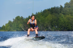 Slim brunette woman riding wakeboard on lake. Young pretty slim brunette woman riding wakeboard on wave of motorboat in a summer lake Stock Photos