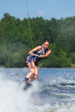Slim brunette woman riding wakeboard on lake Stock Images